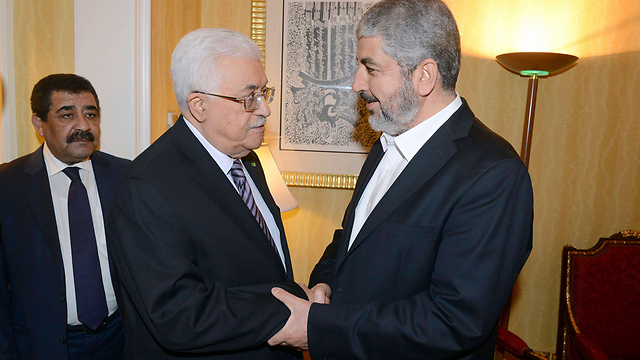 Fatah leader and PA President Abbas with Hamas leader Mashal in Doha (Photo: Reuters)