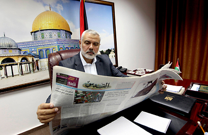 Hamas leader Ismail Haniyeh reading pro-Fatah paper Al-Quds in his Gaza office (Photo: Reuters)