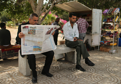 Gaza man reading Al-Quds in a park (Photo: Reuters)