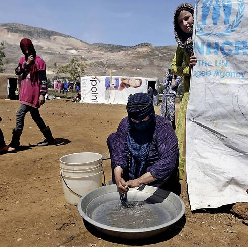 Halbiya, 50, who fled her home from Deir al-Zour, washes her hands after working on a field, at a Syrian refugee camp in Lebanon (Photo: AP) Photo: AP