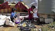 Syrian girls wash dishes outside their tent at a Syrian refugee camp Photo: AP