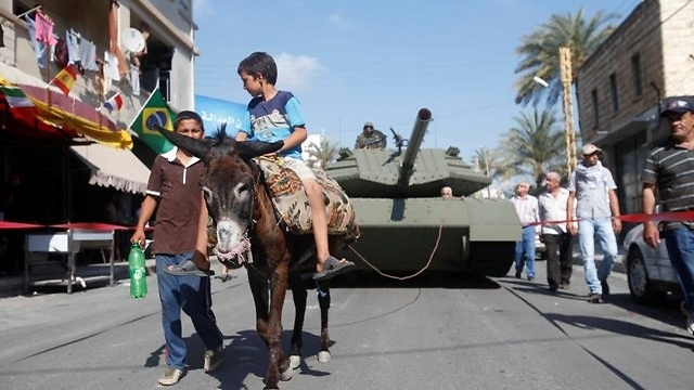 The tank replica dragged through the streets by a donkey