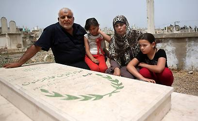 Emad and Rawda Zanoun and their grandchildren Rawda and Farah visit the grave of the girls' father, Alaa Eldin. (Photo: AP)