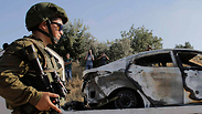 IDF soldier near burnt-out car Photo: Reuters