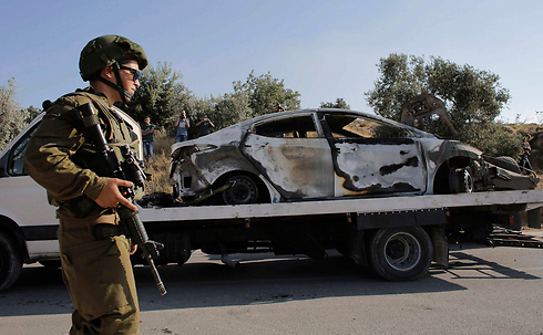 The burned car used in the abduction, found near Dura (Photo: Reuters)