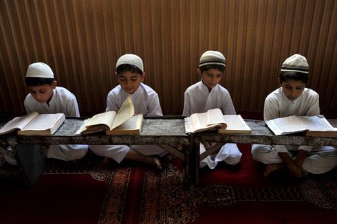 ילדים אפגנים משננים פסוקים מהקוראן בג'ללבאד (צילום: AFP)
