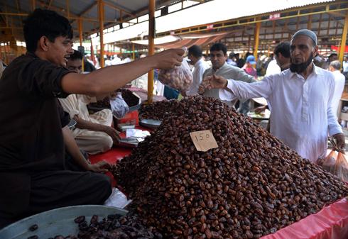 צמים מהבוקר ואוכלים בערב. דוכן תמרים בשוק באיסלאמבד, פקיסטן (צילום: AFP)