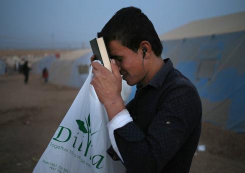 עיראקי מחזיק בספר קוראן במחנה עקורים (צילום: AP)