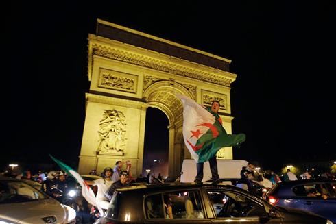 אלג'יראים חוגגים בשער הניצחון בפריז (צילום: רויטרס)