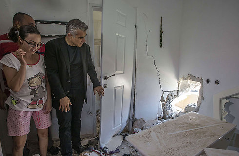 Finance Minister Yair Lapid visiting a home in Sderot that was hit by rocket fire from Gaza. (Photo: AFP) (Photo: AFP)