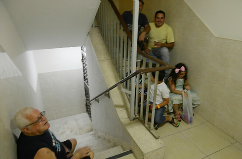 Residents hide amid rocket fire (Photo: Avi Rokach)