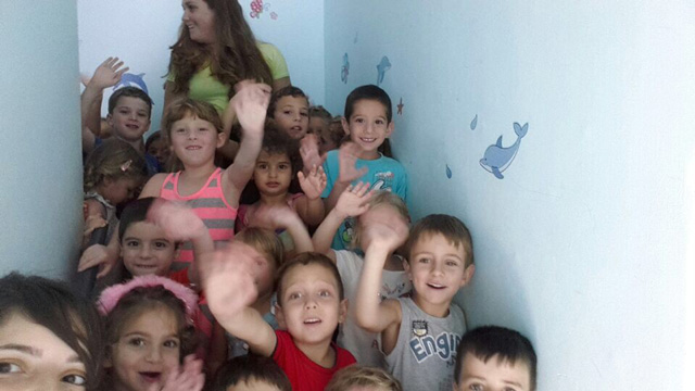 Kindergarteners in Zichron Yaakov wave from shelter (Photo: Noam Bushlin)