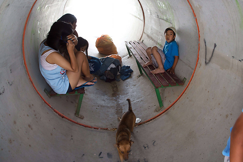 Children taking cover in a portable bomb shelter (Photo: AFP)