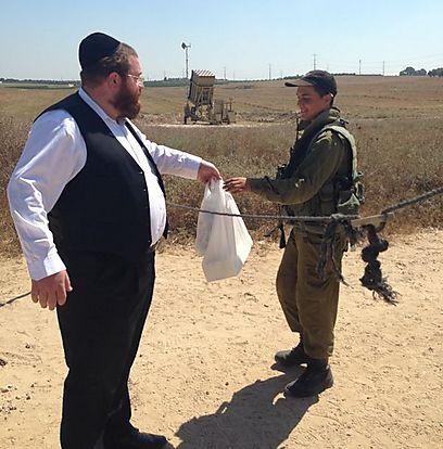 """שימי גשייד, מנכ""""ל ארגון """"רחשי לב"""", מעביר מזון לשבת לחיילים (צילום: סנדי יודקביץ)"""