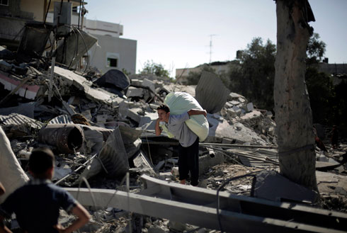 Palestinians rummaging through wreckage of house bombed by IAF (Photo: AP)