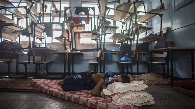 Palestinian man asleep in makeshift bed in UNRWA school (Photo: EPA)