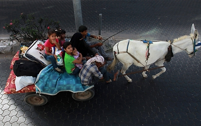 A Gaza family flees their home (Photo: EPA)