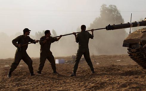 חיילים מנקים לוע טנק מרכבה בצוק איתן (צילום: EPA)