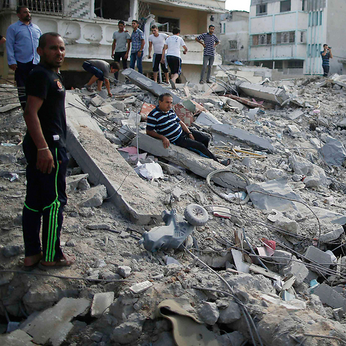 Gazans stand in the rubble of a local neighborhood during Saturday's 12-hour long ceasefire. (Photo: Reuters) Photo: Reuters