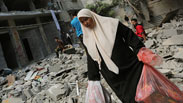 Palestinians survey the destruction in the Saja'iyya neighborhood of Gaza. Photo: EPA