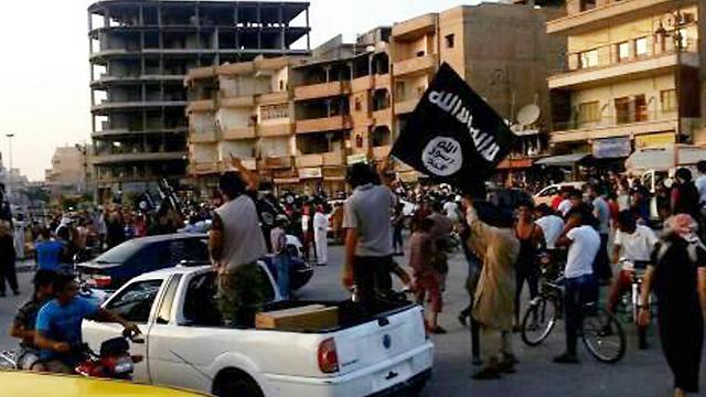 אנשי דאעש בסקילת אישה למוות בראקה (צילום: AP)