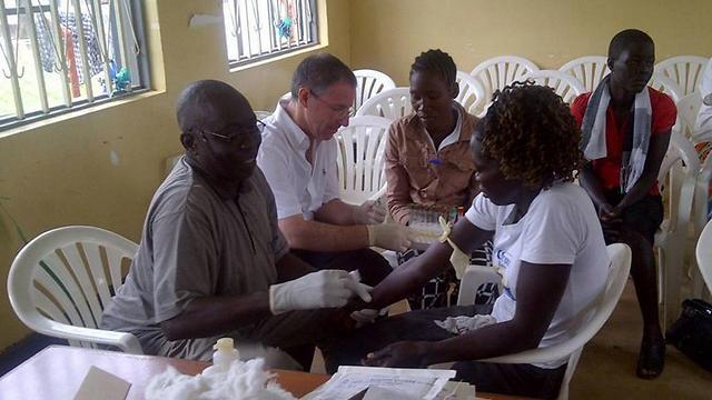 """ד""""ר לסלי לובל נוטל דגימות דם מאפריקאים שהחלימו מאבולה ()"""