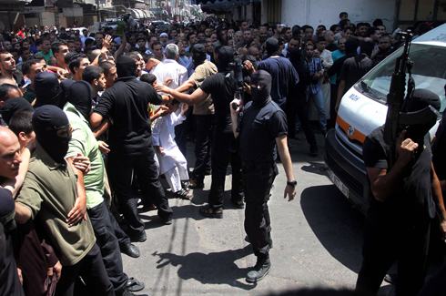 Hamas men following Friday's execution (Photo: AFP) Photo: AFP