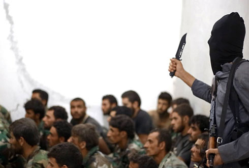 An ISIS militant brandishes a knife over captured Syrian soldiers. (Photo: AP) Photo: AP
