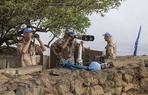 UN Peacekeepers use binoculars to watch the Syrian side of the Golan (Photo: Jack Guez/AFP)