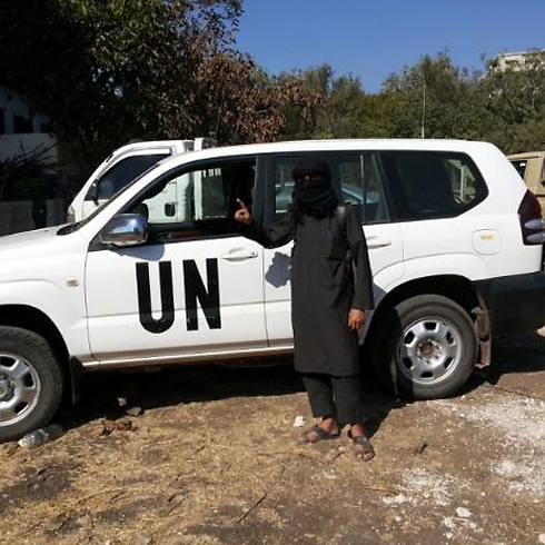 A jihadist in Syria next to a captured UN vehicle.