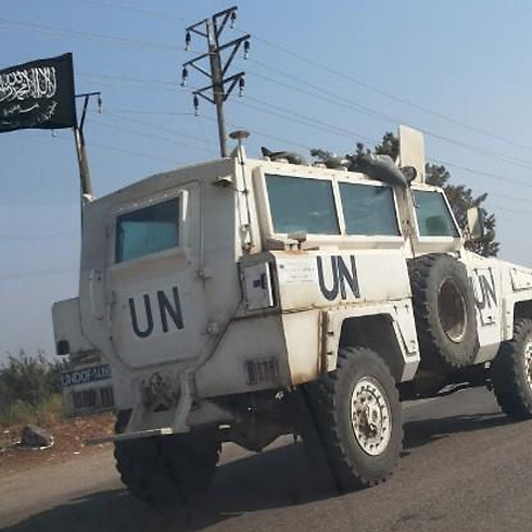 Jabhat al-Nusra flag waving from UN armored vehicle