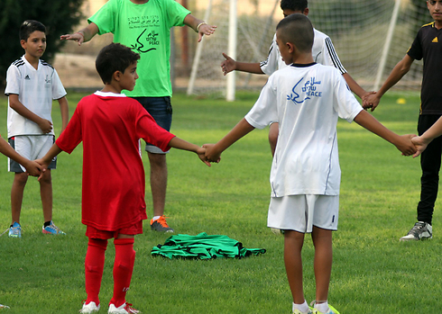 Israeli and Palestinian kids hold hands (Photo: Roi Idan)