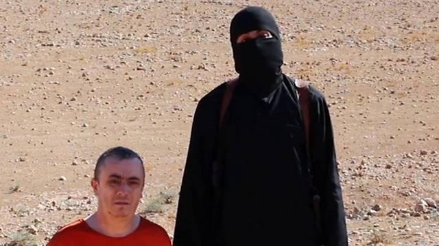 איש דאעש בהוצאתו להורג של השבוי הבריטי אלן הנינג (צילום: AP)