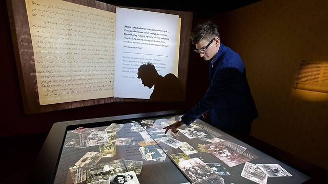 A museum's employee explains artefacts at the Core exhibition in the Museum of the History of Polish Jews (Photo: AFP)