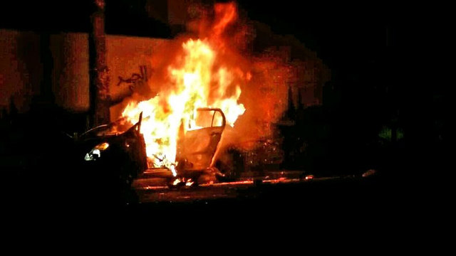 Car in flames following the aborted lynching.