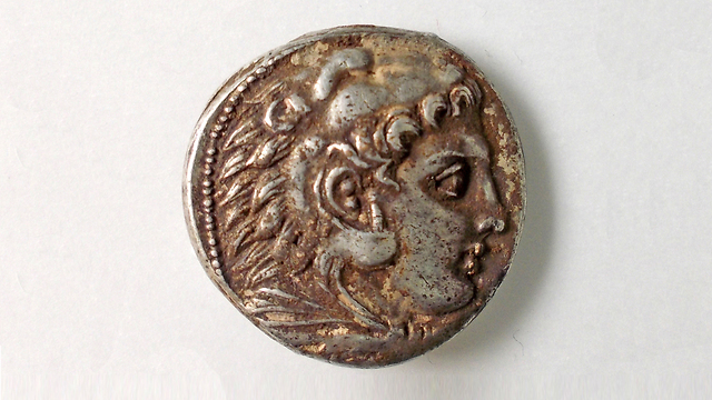 The face of Heracles on coin that was uncovered (Photo: Robert Kool, courtesy of the Israel Antiquities Authority)