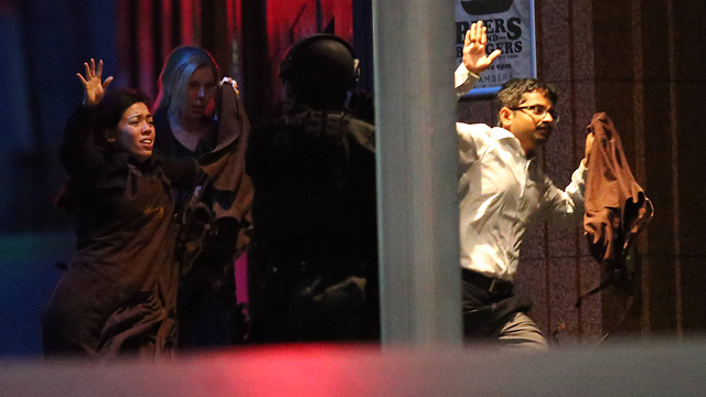 Hostages flee the cafe (Photo: AP)