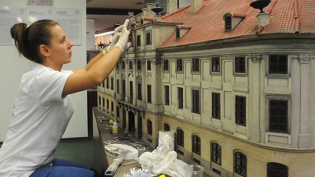 A worker finishes one of the miniature replicas of a lost building (Photo: AP Photo/Alik Keplicz)