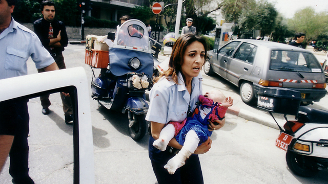 The photo that moved an entire nation - policewoman Ziona Bushri carrying baby Shani after the bombing (Photo: Michael Kremer)