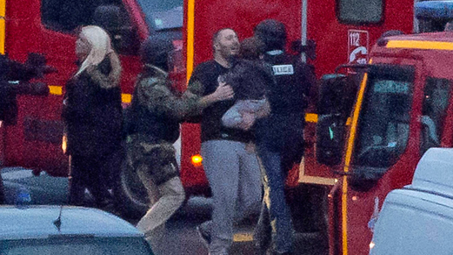 Police and former hostages outside the kosher supermarket during the siege. (Photo: AFP) (Photo: AFP)