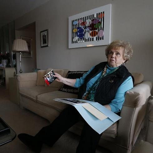 Holocaust survivor and author Paula Burger, sits in living room reminiscing over photos of her children and grandchildren (Photo: AP)