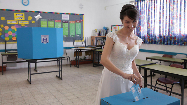 A bride votes in her wedding dress in Holon (Photo: Reuters)