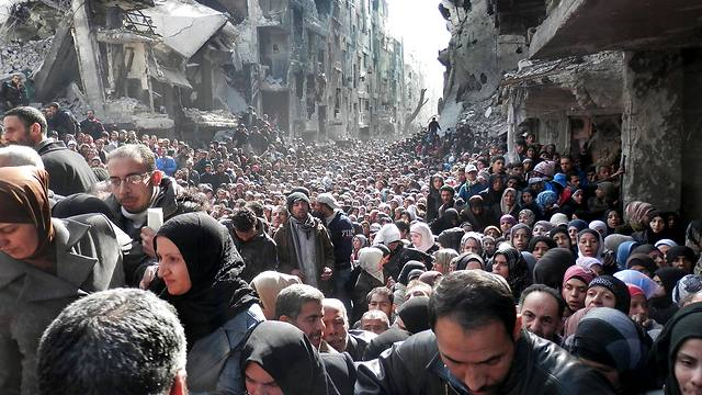 Palestinians at the besieged Yarmouk refugee camp in Damascus, queuing to receive food supplies from UNRWA (Photo: AP)