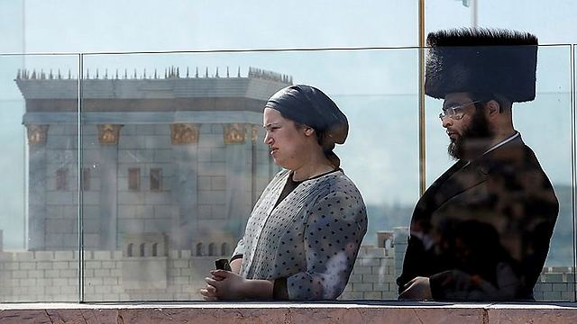 Watching beside a model of the Temple (Photo: AFP)