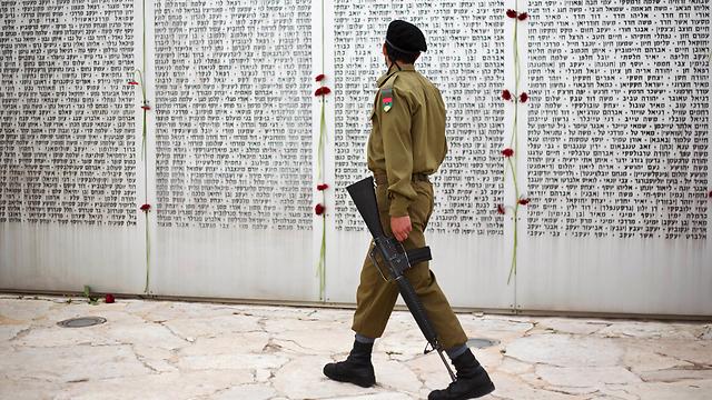 חייל עובר מול לוח הזיכרון בלטרון (צילום: AP)