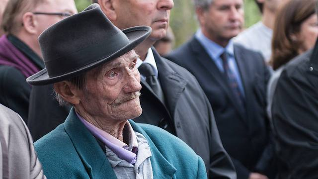 An unidentified Jewish survivor and other guests listen to Hollande during his visit (Photo: EPA)