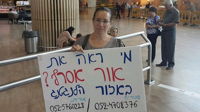 Orit Asraf, mother of Or, at the airport with a sign asking if anyone had seen her son