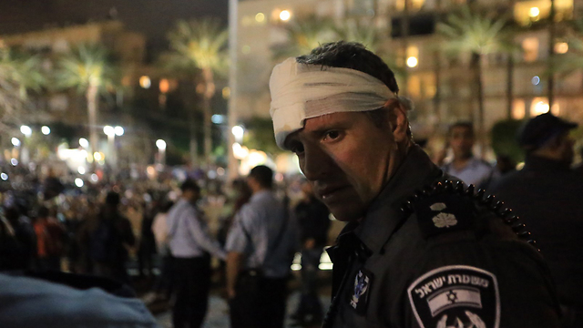 A wounded policeman during the clashes in Rabin Square (Photo: Yaron Brenner)