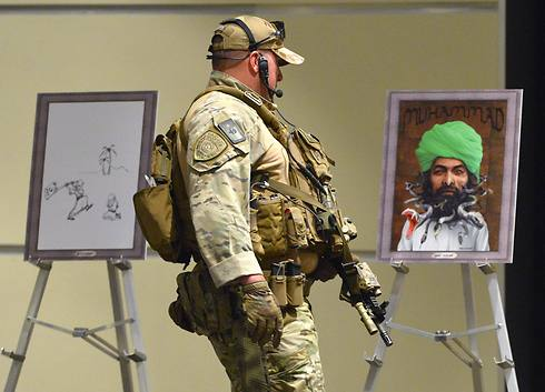 Member of US special forces in front of drawings of Prophet Mohammad at event where shooting took place. (Photo: EPA)