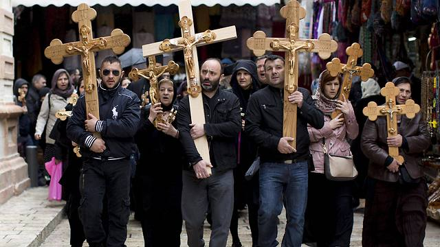 Christian worshipers hold crosses and walk outside the church of the Holy Sepulchre, during the Good Friday procession in the Old City of Jerusalem (Photo: EPA)